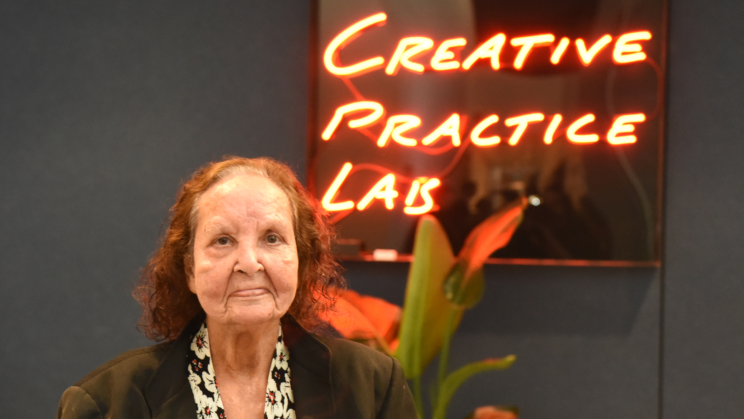 Artist Esme Timbery in front of neon sign