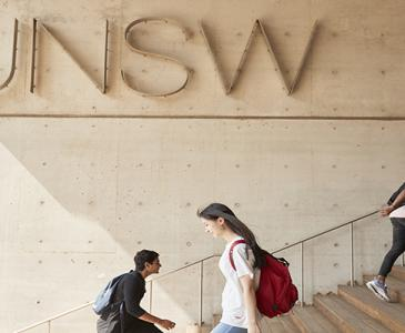 Students walking past UNSW sign