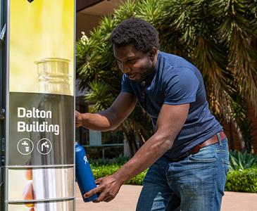 Man filling up drink bottle from UNSW bubbler on University Mall