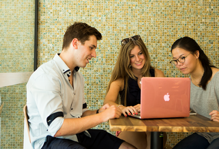 Three UNSW students sitting around a laptop